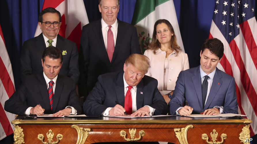 FILE - President Donald Trump sits between Canada's Prime Minister Justin Trudeau, right, and Mexico's President Enrique Pena Nieto as they sign a new United States-Mexico-Canada Agreement that is replacing the NAFTA trade deal, Nov. 30, 2018.