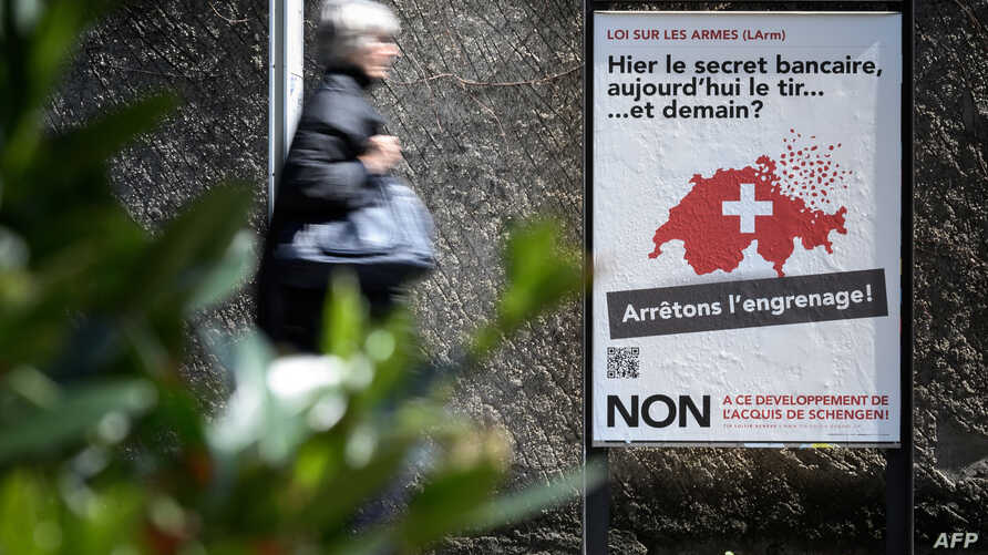 """A woman walks past a campaign poster against toughening gun laws in Switzerland. It reads in French, """"Yesterday banking secrecy, today shooting ... and tomorrow? Let's stop the spiral!"""" May 13, 2019, in Geneva."""