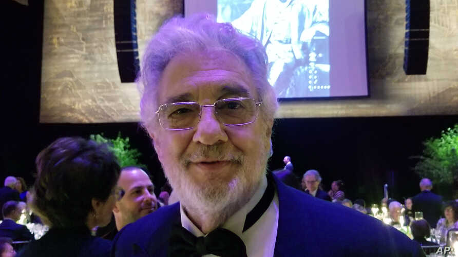 """Tenor Placido Domingo poses for a photo against the backdrop of himself as a younger singer as Verdi's """"Otello,"""" Sunday, April 28, 2019, at the Metropolitan Opera, in New York. Domingo has starred on the stage of the Metropolitan Opera for a whopping..."""