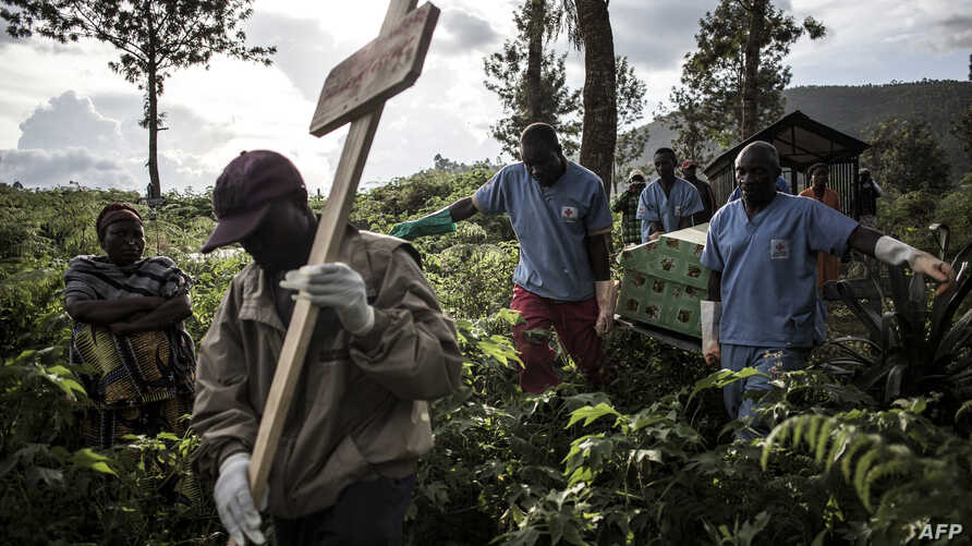 FILE - Health workers carry a coffin containing a victim of the Ebola virus on May 16, 2019 in Butembo.
