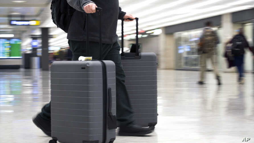 FILE - In this March 26, 2019, file photo, an airline passenger walk in the arrivals terminal at Dulles International Airport in Dulles, Virginia. Newly documents filed in a federal lawsuit claim that U.S. government searches of phones and laptops a...