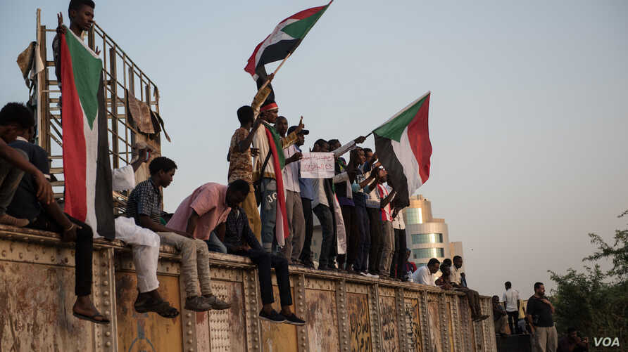 Protesters chant and wave Sudanese flags as dusk approaches on the first day of Ramadan May 6, 2019, at the sit-in in Khartoum, Sudan.