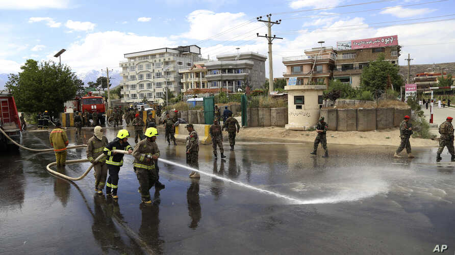 Afghan firefighters clean the site of a suicide bombing targeting a military academy in Kabul, Afghanistan, Thursday, May 30, 2019. The suicide bomb killed at least six people and wounded six others on Thursday, the Interior Ministry said. (AP Photo)