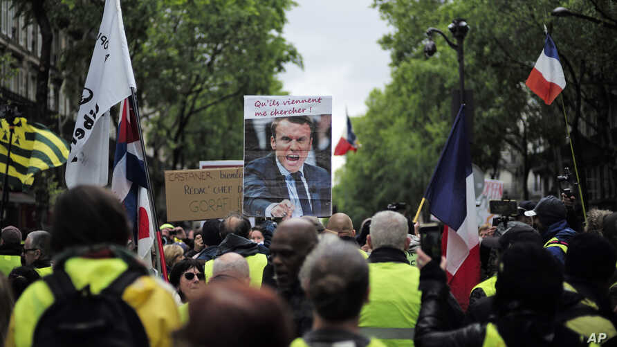 "Yellow vest protesters, one carrying a placard with a picture and a quote of French President Emmanuel Macron (""Let them come get me""), march in Paris, May 4, 2019."