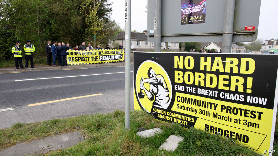 Protesters against Brexit and the possible imposition of any hard border between Northern Ireland and Ireland gather with a banner at the border between Derry (Londonderry) in Northern Ireland and County Donegal in the Republic of Ireland near the Ir...
