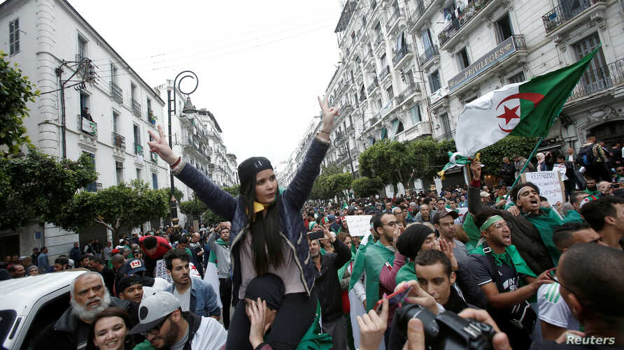 Demonstrators hold flags and banners during peaceful anti-government protests in Algiers, Algeria, May 3, 2019.
