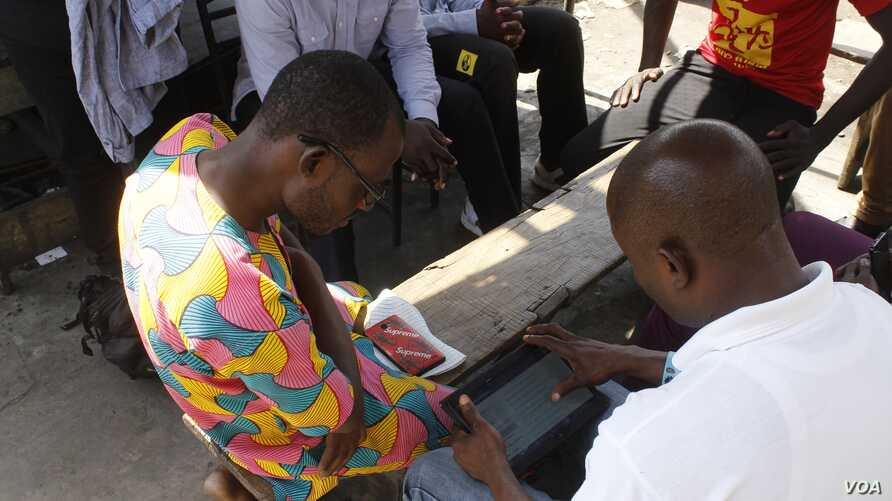 A government official tests an electronic questionnaire in Old Fadama, Accra's largest slum, ahead of Ghana's first digital population and housing census in 2020, May 24, 2019.