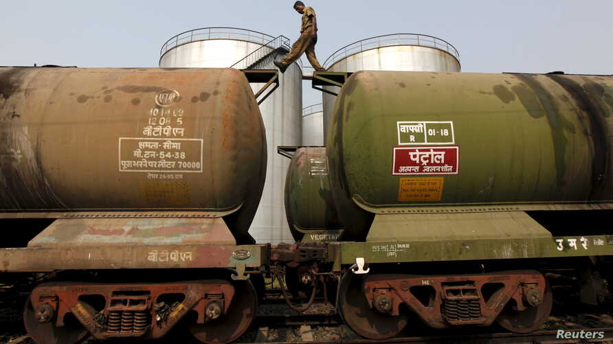 FILE - A worker walks atop a tanker wagon to check the freight level at an oil terminal on the outskirts of Kolkata, India, Nov. 27, 2013.