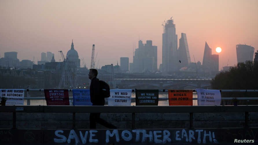 FILE - FILE PHOTO: A commuter walks along Waterloo Bridge, which is being blocked by climate change activists, during the Extinction Rebellion protest in London, Apr. 17, 2019.