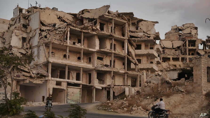 Motor cycles ride past buildings destroyed during the fighting in the northern town of Ariha, in Idlib province, Syria, Sept.20, 2018.