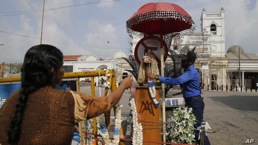 A Sri Lankan navy officer helps a Catholic devotee offer a garland outside St. Anthony's Church, one of the targets of Easter Sunday attacks in Colombo, Sri Lanka,  May 5, 2019.