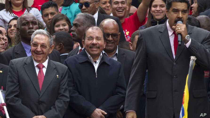 Cuba's President Raul Castro, left, and Nicaragua's President Daniel Ortega, second left, listen to a speech by Venezuela's President Nicolas Maduro, outside of Miraflores palace during a rally in Caracas, Venezuela, March 5, 2018.