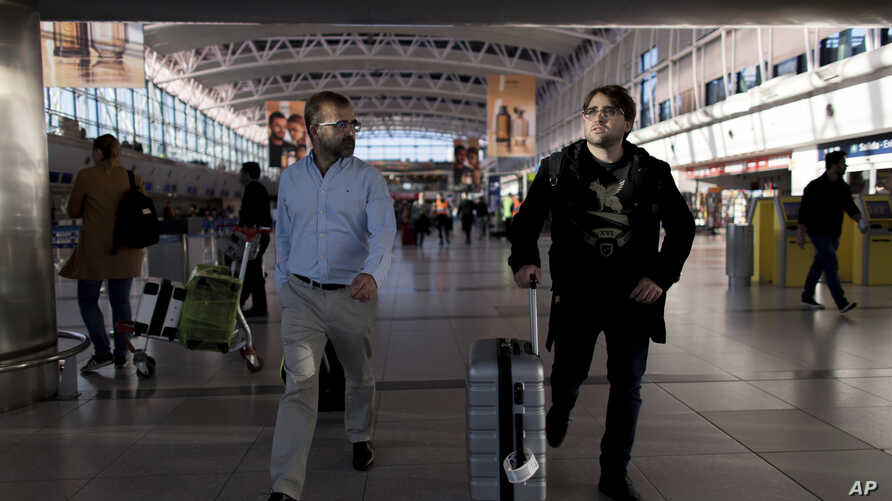 Tomas Ruiz pushes his suitcase as he is accompanied by his father, Pablo, at the International Airport Ministro Pistarini before boarding a plane to Ireland, in Ezeiza, Argentina, April 4, 2019.