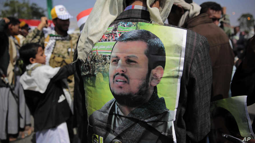 A Supporter of Houthi Shiites displays a poster of Abdel-Malek al-Houthi, the leader of Yemen's Shiite rebels, on his jacket during a rally to mark the third anniversary of the Houthis' takeover of the Yemeni capital, in Sanaa, Yemen, Sept. 21, 2017....