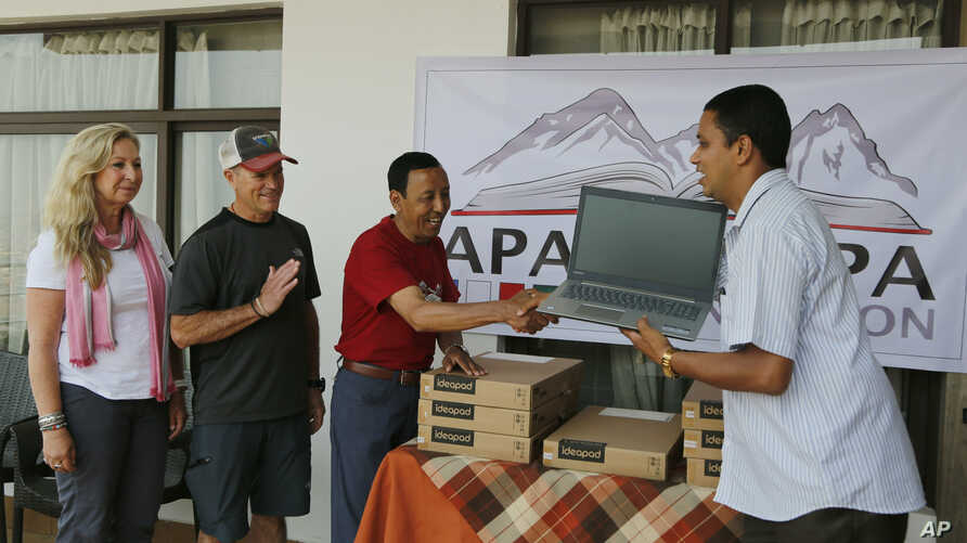 In this May 9, 2019, photo, Apa Sherpa, center, hands over a computer to Chakra Karki, representative of a school from Dhuske, Okhaldhunga district in Kathmandu, Nepal.