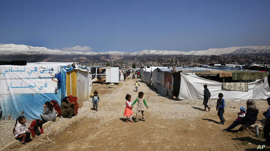 FILE - Refugees from Syria are seen outside their tents, in the town of Saadnayel, east Lebanon, April 23, 2019.
