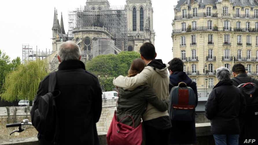 People hug while looking at Notre-Dame-de-Paris in the aftermath of a fire that devastated the cathedral, April 16, 2019.