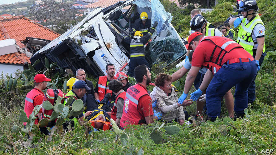 Firemen help victims of a tourist bus crash, April 17, 2019, in Caniço, on the Portuguese island of Madeira.