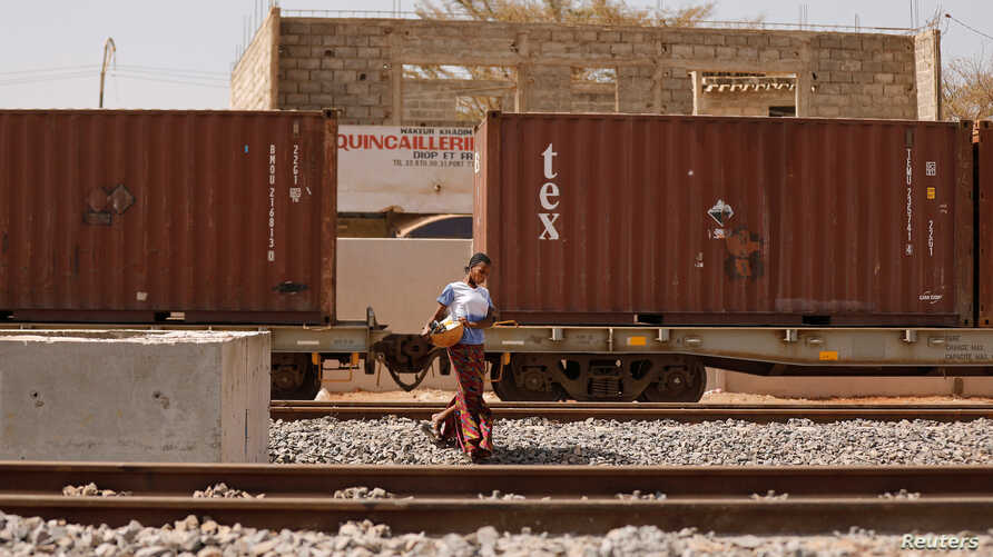 FILE - A woman walks along newly built tracks of the high speed railway in Mbao, on the outskirts of Dakar, Senegal, Feb. 12, 2019.