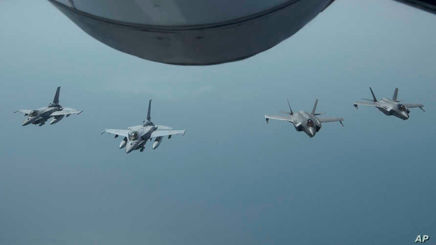 FILE - In this May 29, 2019, photo, released by the U.S. Air Force, United Arab Emirates Air Force Desert Falcons fly in formation with U.S. F-35A Lightning IIs in an undisclosed location in Southwest Asia.