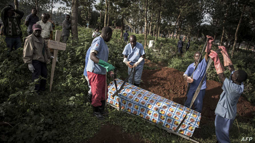 FILE - Health workers prepare to bury a coffin containing a victim of the ebola virus on May 16, 2019 in Butembo, DRC.