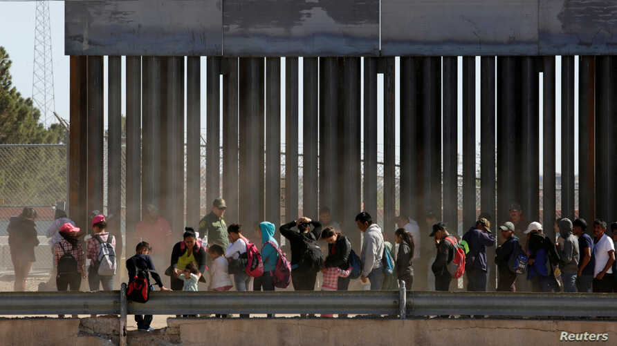 FILE - Migrants queue to request asylum after crossing illegally into El Paso, in this picture taken from Ciudad Juarez, Mexico, April 21, 2019.