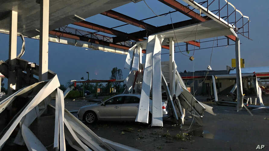 A car is trapped under the fallen metal roof of the Break Time gas station and convenience store in tornado-hit Jefferson City, Mo., May 23, 2019.