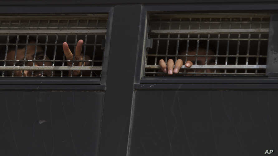 FILE - Palestinian prisoners are seen aboard an Israeli Prisons Service bus, soon to be exchanged for a captured Israeli soldier in   southern Israel's Negev desert, in October 2011. It was announced April 27, 2019, that Israel would release twopri...