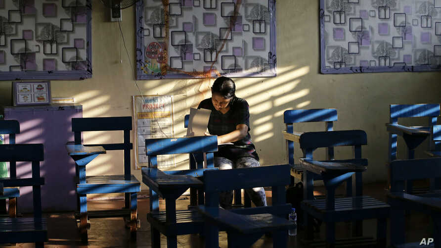 A Filipino woman votes during the country's midterm elections inside a polling center at a school in Manila, Philippines on Monday, May 13, 2019.