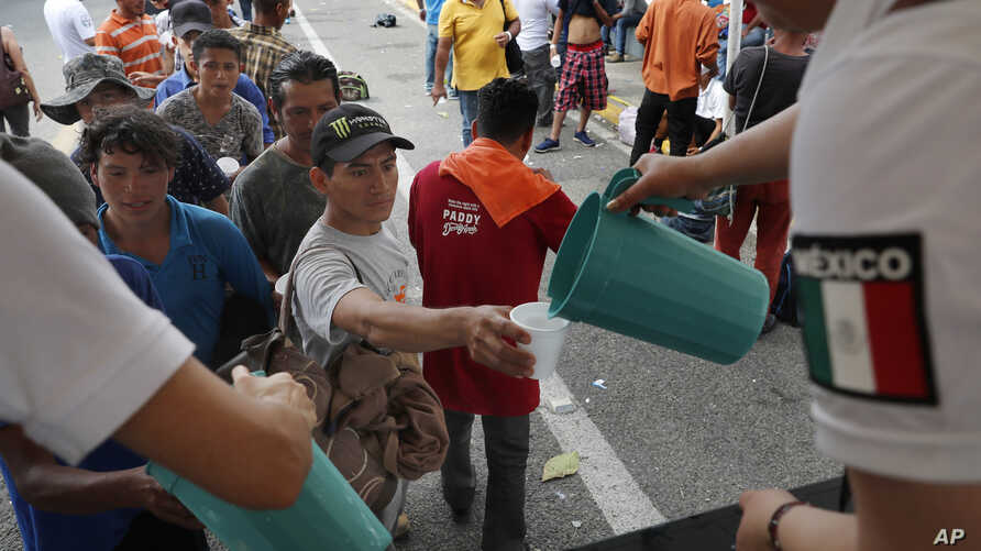 Central American migrants eat lunch, courtesy of Mexican officials, on the border bridge between Mexico and Guatemala, as they wait for their humanitarian visas from Mexican migration officials to be processed.