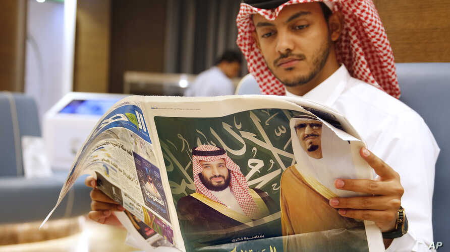 A man reads a newspaper with pictures of Saudi King Salman, right, and his Crown Prince Mohammed bin Salman, at the press center for the upcoming Arab and Islamic summits in Mecca, Saudi Arabia, May 30, 2019.