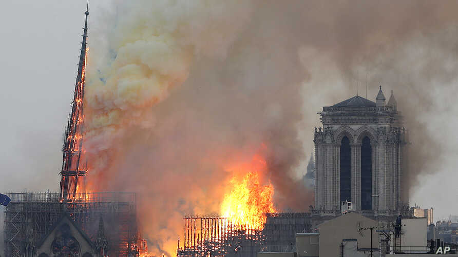 FILE - Flames rise from Notre Dame cathedral as it burns in Paris, Apr. 15, 2019.