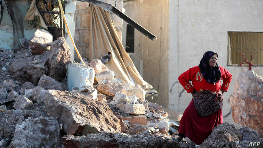 A woman stands amid the rubble of a building that was reportedly destroyed during air strikes by the Syrian regime ally Russia, in the town of Kafranbel in the rebel-held part of the Syrian Idlib province, May 20, 2019.