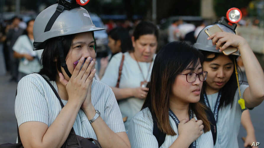 Wearing protective helmets, employees evacuate their office building following an earthquake in Manila, Philippines, Apr. 22, 2019.