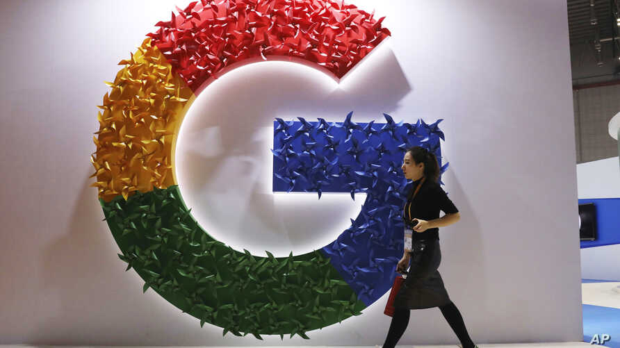 FILE - A woman walks past the logo for Google at the China International Import Expo in Shanghai, Nov. 5, 2018.