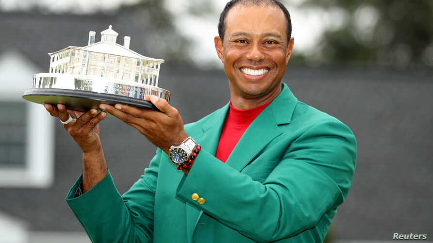 Golf - Masters - Augusta National Golf Club - Augusta, Georgia, U.S. - April 14, 2019. Tiger Woods of the U.S. celebrates with with his green jacket and trophy after winning the 2019 Masters. REUTERS/Lucy Nicholson TPX IMAGES OF THE DAY - RC150847653...