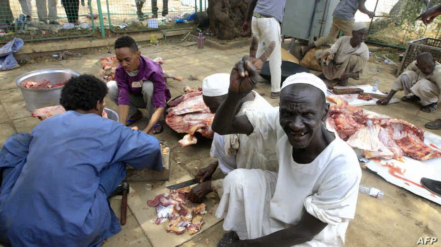 Sudanese protesters cut the meet of sheep and cows that they slaughtered on April 16, 2019, as they celebrate the ousting of longtime leader Omar al-Bashir, outside the army complex in the capital Khartoum, where they have been camping out for days.