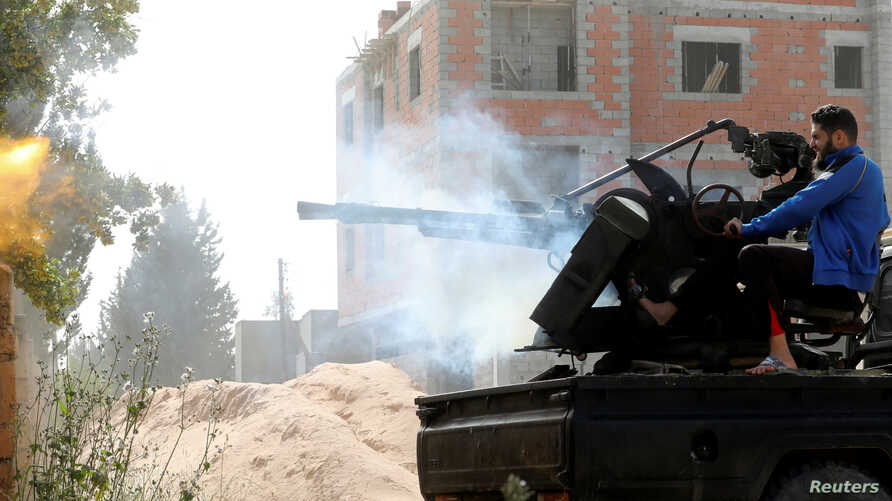 A member of the Libyan internationally recognized government forces fires during a battle with eastern forces in Ain Zara, Tripoli, Libya, April 25, 2019.