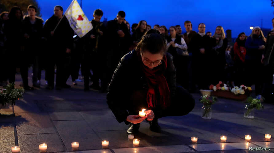 A woman places a candle with others at the Place Saint-Michel the day after Notre-Dame Cathedral suffered heavy damage from a massive fire that devastated large parts of the gothic structure in Paris, France, April 16, 2019.