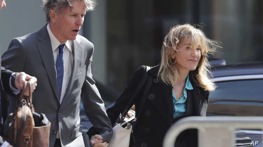 FILE - Actress Felicity Huffman arrives holding hands with her brother Moore Huffman Jr., left, at federal court in Boston, Massachusetts, April 3, 2019, to face charges in a nationwide college admissions bribery scandal.