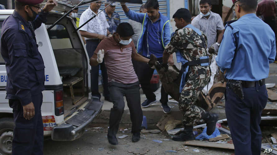 The body of a victim is removed from the site of an explosion in Kathmandu, Nepal, May 26, 2019.