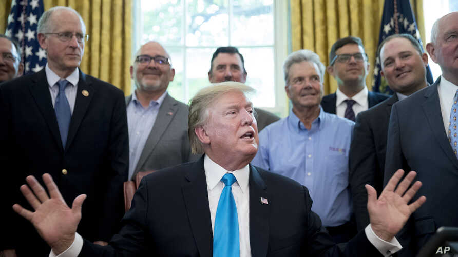President Donald Trump, accompanied by Rep. Mike Conaway, R-Texas, left, Agriculture Secretary Sonny Perdue, right, and farmers and ranchers, speaks in the Oval Office of the White House, May 23, 2019, in Washington.