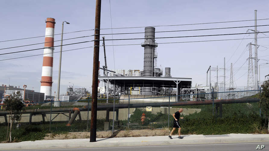 A jogger runs past the Scattergood power plant, Feb. 12, 2019, in Los Angeles. Los Angeles will abandon a plan to spend billions rebuilding three natural gas power plants as the city moves toward renewable energy, Mayor Eric Garcetti said Monday.