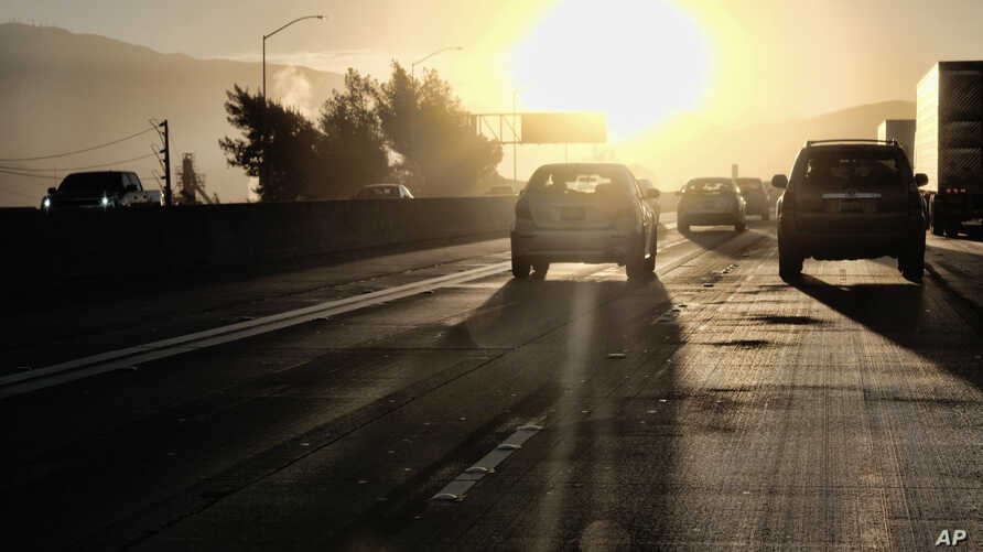 In this August 31, 2018, photo, morning commuters drive into downtown Los Angeles as the sun rises along Interstate 5.