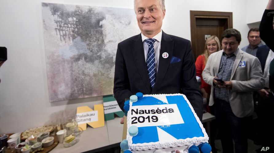 Economist Gitanas Nauseda, a presidential candidate, holds a cake as they celebrate his win in the first round of Lithuania's presidential election in office in Vilnius, Lithuania, early Monday, May 13, 2019.