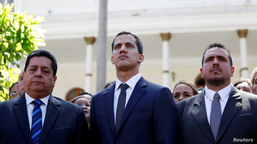 FILE - Juan Guaido, new President of the National Constituent Assembly and lawmaker of the Venezuelan opposition party Popular Will, flanked by lawmakers Edgar Zambrano, left, of Democratic Action party, and Stalin Gonzalez of A New Time party, in Ca...