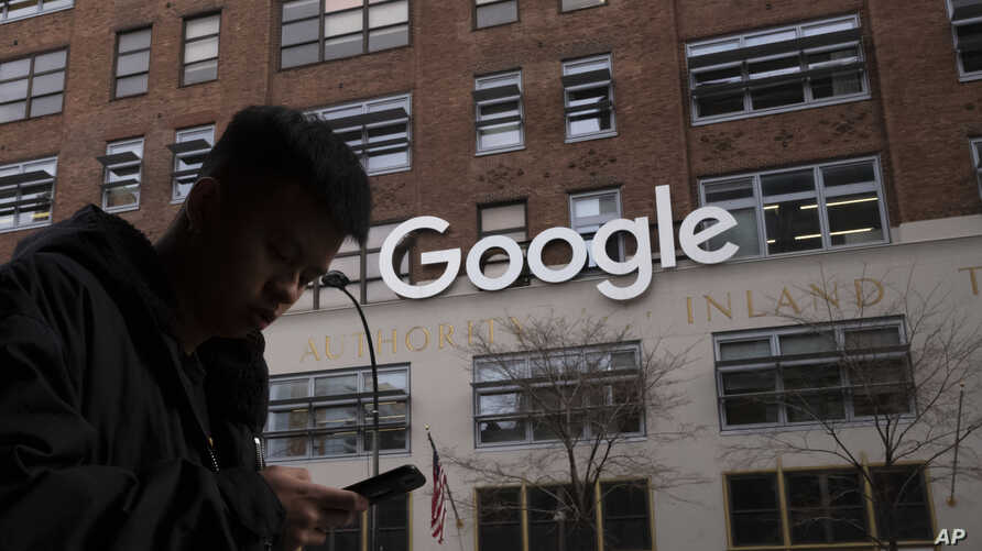 A man using a mobile phone walks past Google offices in New York, Dec. 17, 2018. Executives from Google and Facebook are facing Congress Tuesday, April 8, 2019, to answer questions about their role in the hate crimes and the rise of white nationalis...