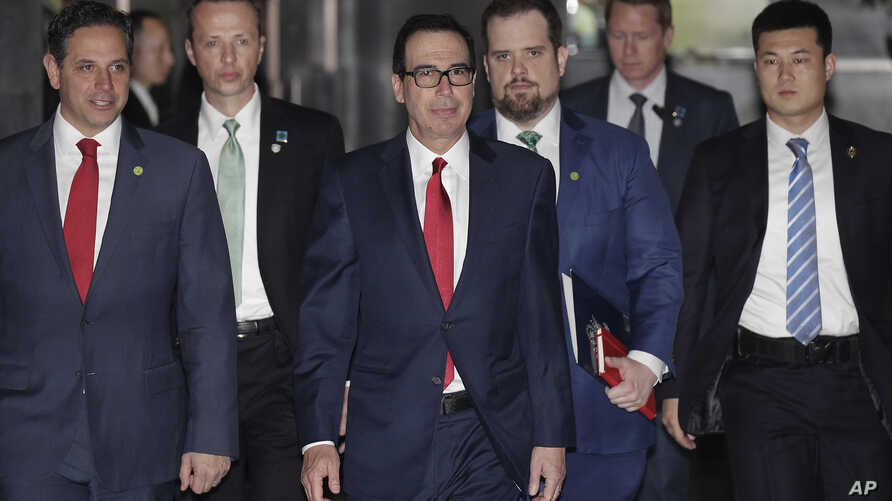 U.S. Treasury Secretary Steven Mnuchin, center, escorted by bodyguards and a delegation leaves a hotel in Beijing, Friday, March 29, 2019.