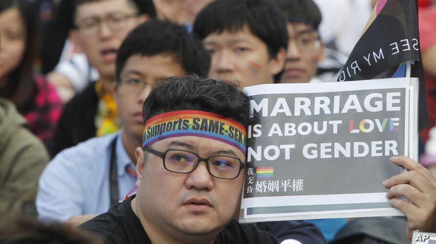 FILE - A supporter of LGBT and human rights holds a slogan during a rally supporting a proposal to allow same-sex marriage in Taipei, Taiwan, Dec. 10, 2016. Taiwanese legislators are scheduled to decide Friday on legalizing same-sex marriage, marking...