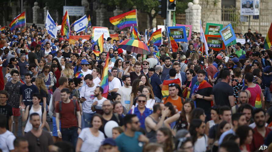 Participants wave flags and hold signs during the annual Gay Pride parade in Jerusalem, June 6, 2019.